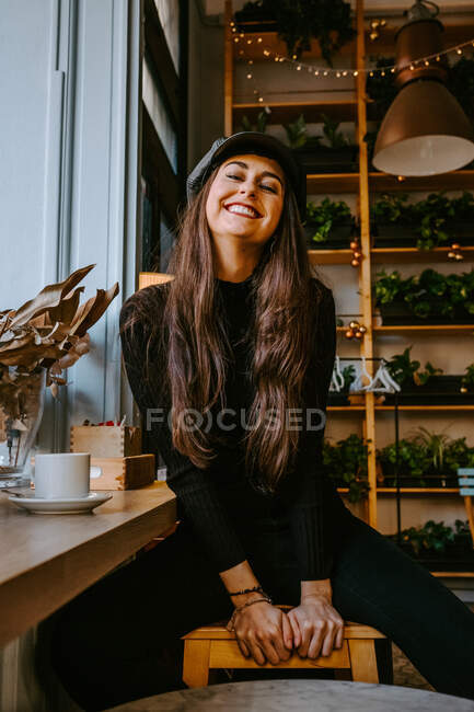 Positive young woman in trendy outfit smiling and looking at camera while sitting on stool near window in cozy cafe — Stock Photo