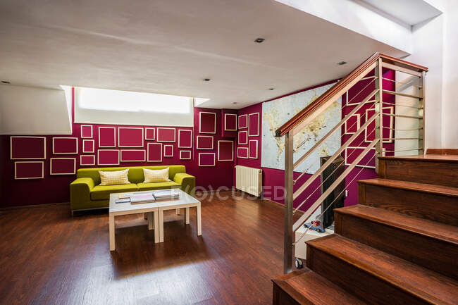Contemporary living room with wooden floor and with bright green sofa and geometric elements on red walls — Stock Photo