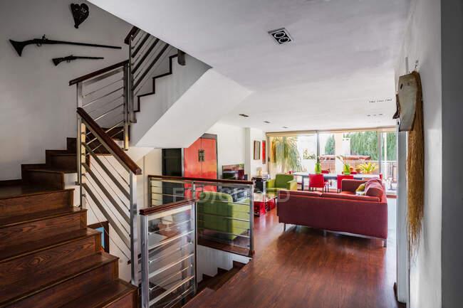 Сучасна вітальня в червоному і зеленому кольорах з великим диваном. — стокове фото