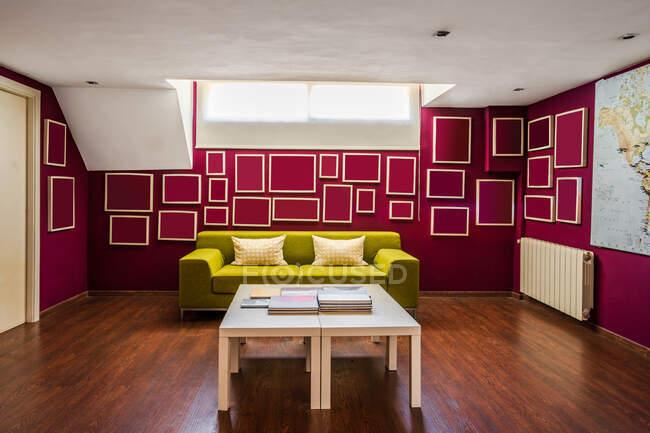Salón contemporáneo con suelo de madera y con sofá verde brillante y elementos geométricos en las paredes rojas - foto de stock