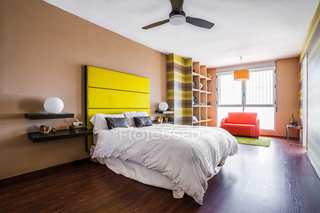 Comfortable bed with bright yellow headboard in modern studio apartment decorated in minimalist style — Stock Photo