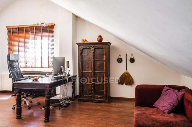 Рабочее место с винтажной деревянной мебелью и восточным декором в современной квартире — стоковое фото