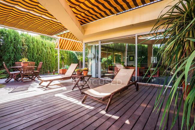 Salotti in legno e tavolo con sedie collocati sulla spaziosa terrazza della moderna casa di campagna circondata da piante verdi — Foto stock