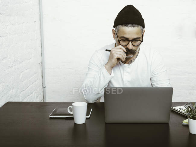Concentrated bearded male in glasses and headwear using netbook for working at home at quarantine time — Stock Photo