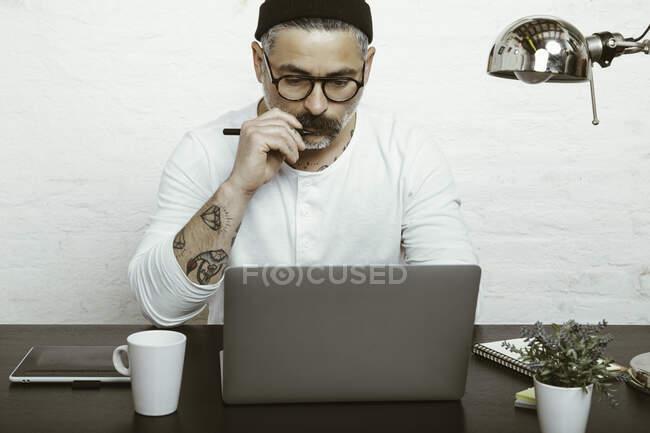 Maschio barbuto concentrato in occhiali e copricapo con netbook per lavorare a casa in quarantena — Foto stock
