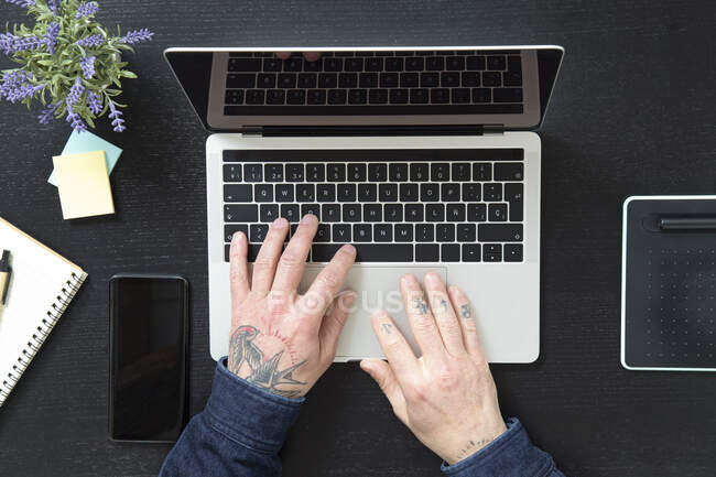 From above anonymous male typing on laptop keyboard while sitting at table and working on project in at home during quarantine — Stock Photo
