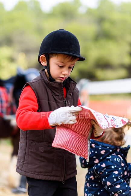 Petit garçon en casque de jockey et gants portant un coussin de selle doux pendant les cours d'école d'équitation — Photo de stock