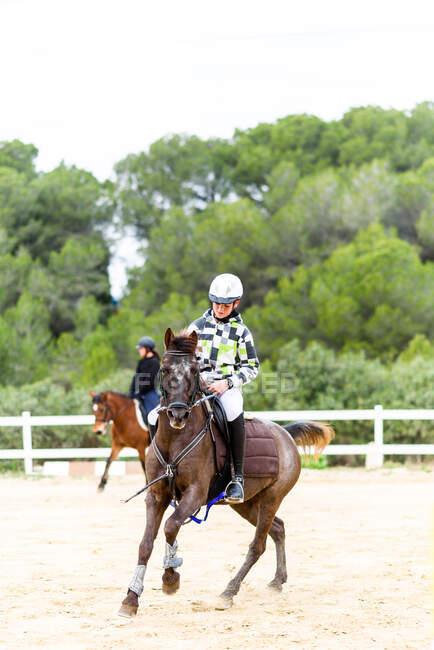 Мальчик-жокей в шлеме катается на коричневой лошади на выездной арене во время тренировки в конной школе — стоковое фото