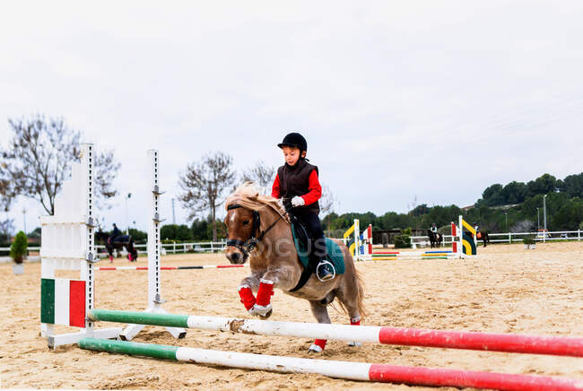 Pequeno jóquei no capacete sentado em pônei romano enquanto saltava sobre pólos listrados contra o céu nublado durante o treinamento de equitação na escola equestre — Fotografia de Stock