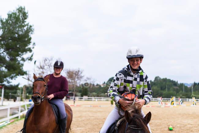 Счастливые подростки-жокеи в шлемах общаются друг с другом, катаясь на покорных лошадях на песчаной арене во время урока в конной школе — стоковое фото