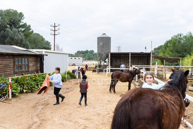 Group of children preparing horses for ride in enclosure before training on ranch of equestrian school — Stock Photo