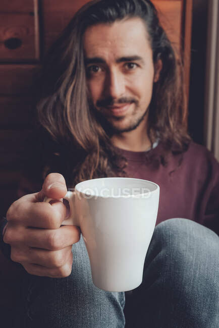 Bearded man resting with hot beverage — Stock Photo
