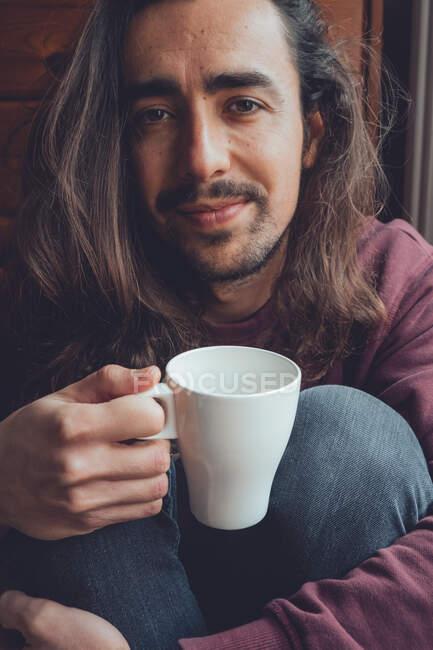Бородатый мужчина отдыхает с горячим напитком — стоковое фото