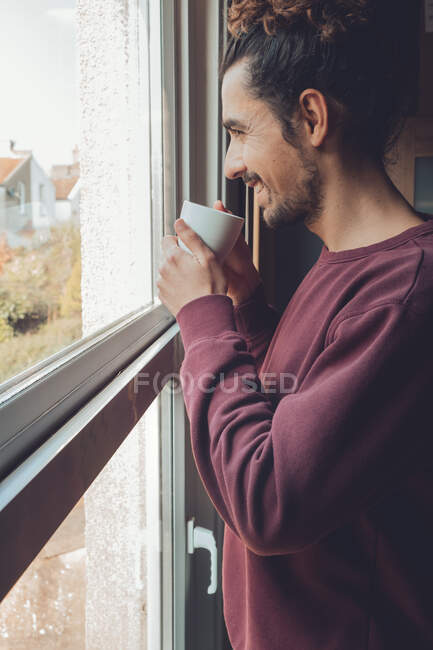 Adulto macho com caneca olhando para fora janela — Fotografia de Stock