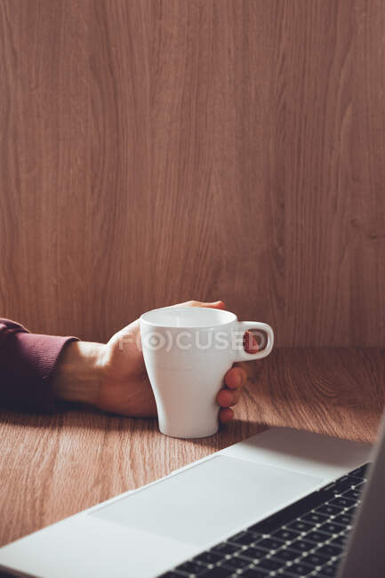 Unrecognizable male freelancer with cup of hot beverage browsing laptop while working on remote project at home — Stock Photo