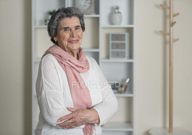 Elderly woman in pink scarf looking at camera with arms crossed while staying at home during coronavirus pandemic — Stock Photo