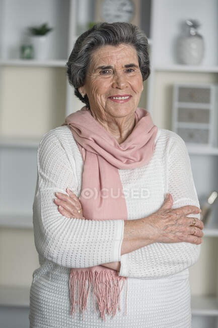 Happy elderly woman in pink scarf looking at camera with arms crossed while staying at home during coronavirus pandemic — Stock Photo