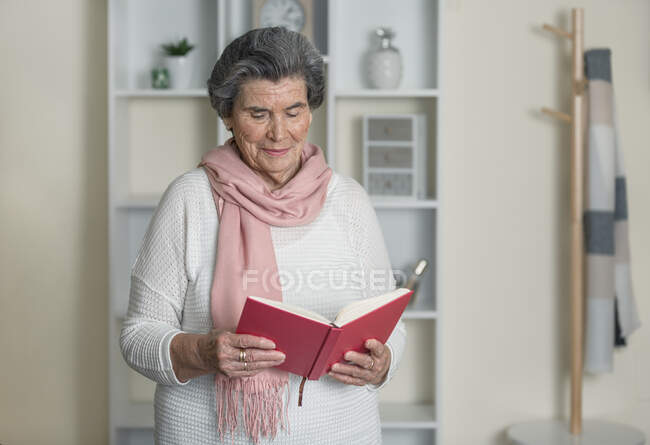 Elderly lady with pink scarf reading interesting book while standing in cozy room at home — Stock Photo