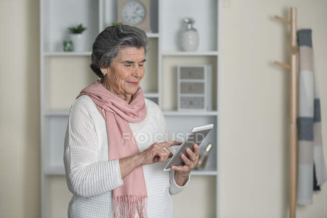 Friendly elderly lady with contemporary tablet in cozy room at home — Stock Photo