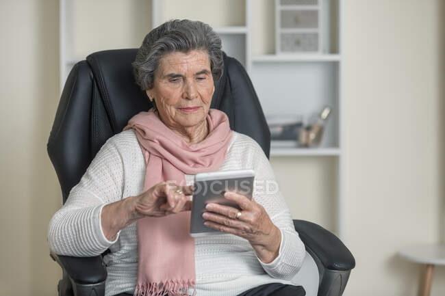Positive senior woman in pink scarf smiling while sitting on comfortable chair in cozy room at home — Stock Photo