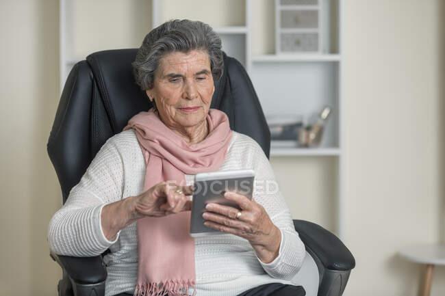 Donna anziana positiva in sciarpa rosa sorridente mentre seduto su una comoda sedia in camera accogliente a casa — Foto stock