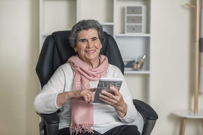 Positive senior woman in pink scarf smiling and looking at camera while sitting on comfortable chair in cozy room at home — Stock Photo