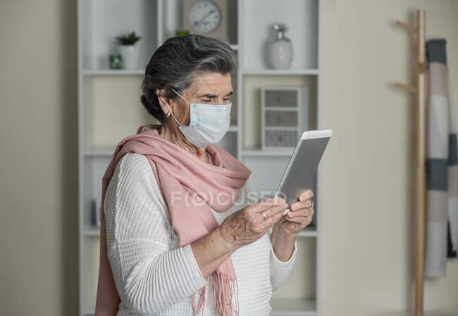 Senior female with medical mask using video chat app on smartphone during coronavirus pandemic at home — Stock Photo