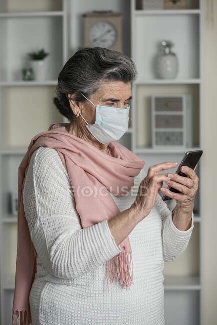 Femme âgée avec masque médical utilisant l'application de chat vidéo sur smartphone pendant la pandémie de coronavirus à la maison — Photo de stock