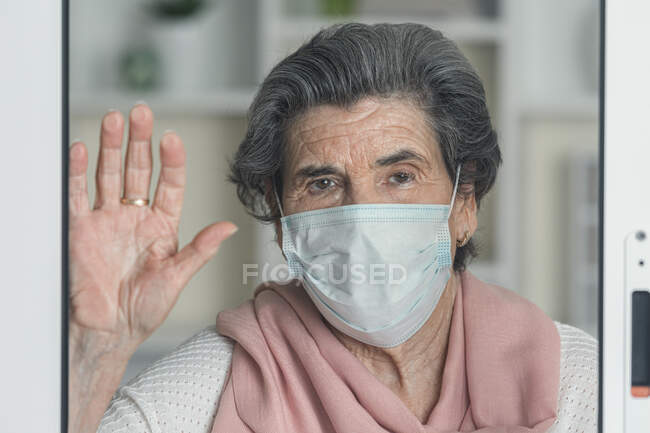 Elderly lady in medical mask waving looking at camera throughout the windows while staying at home during coronavirus epidemic — Stock Photo