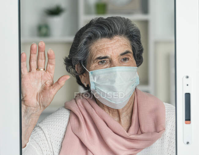 Elderly lady in medical mask waving looking away throughout the windows while staying at home during coronavirus epidemic — Stock Photo