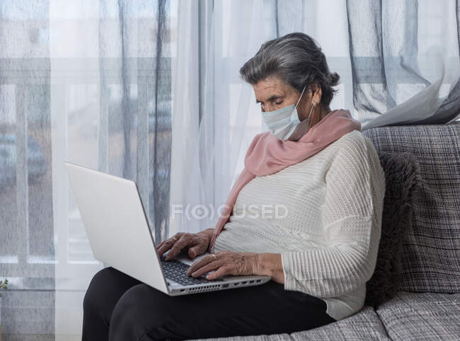Senior female in medical mask sitting on couch and browsing laptop while staying at home during coronavirus pandemic — Stock Photo