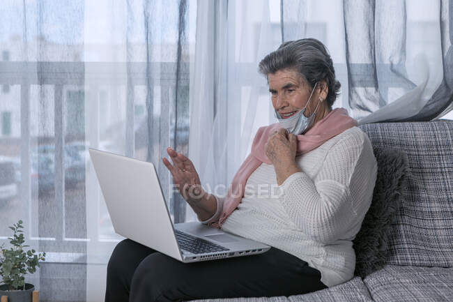 Senior female in medical mask sitting on couch and doing video call through laptop while staying at home during coronavirus pandemic — Stock Photo