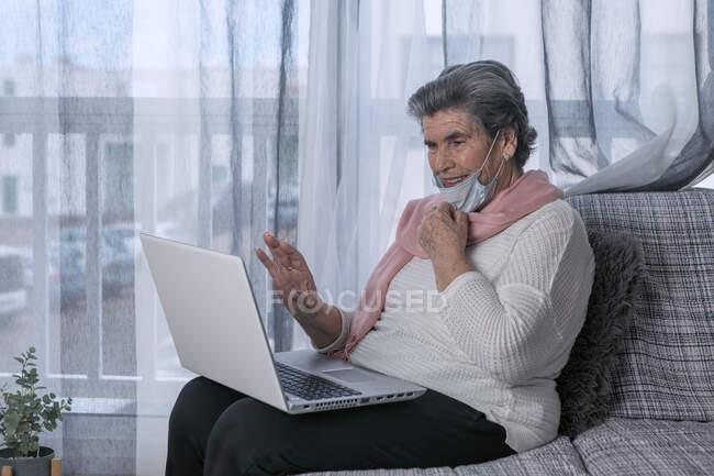 Старшая женщина в медицинской маске, сидящая на диване и делающая видеозвонки через ноутбук, находясь дома во время пандемии коронавируса — стоковое фото