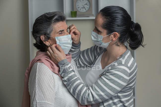 Молодая женщина в повседневной одежде надевает медицинскую маску на пожилую женщину из группы риска, находясь дома во время пандемии коронавируса — стоковое фото