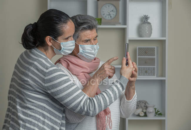 Grandmother and granddaughter in medical mask using mobile phone to call to relatives while staying at home during coronavirus epidemic — Stock Photo