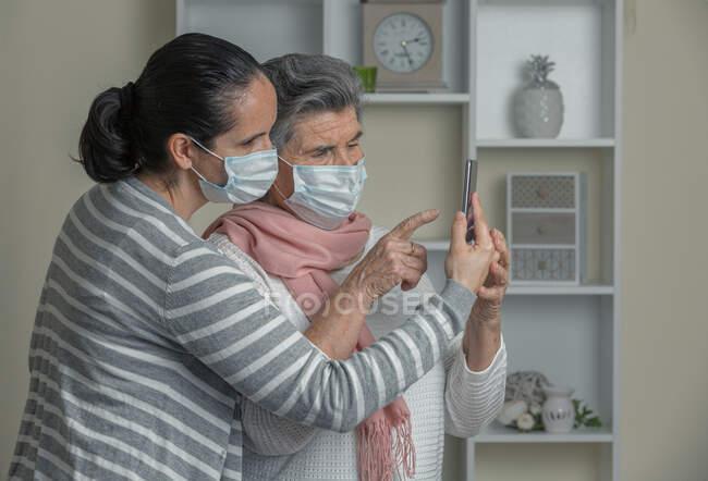 Avó e neta em máscara médica usando telefone celular para chamar os parentes durante a estadia em casa durante a epidemia de coronavírus — Fotografia de Stock