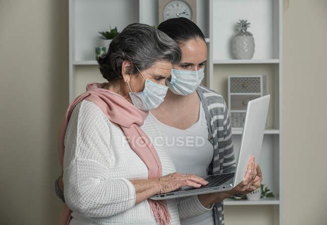 Бабушка и внучка в медицинской маске с помощью ноутбука звонят родственникам, находясь дома во время коронавируса. — стоковое фото