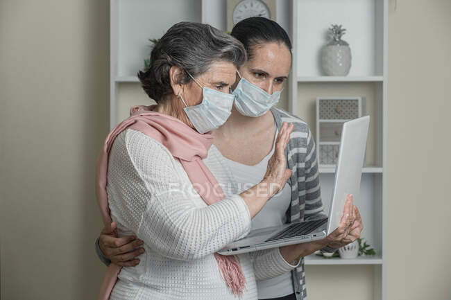 Grandmother and granddaughter in medical mask using laptop to call to relatives while staying at home during coronavirus epidemic — Stock Photo