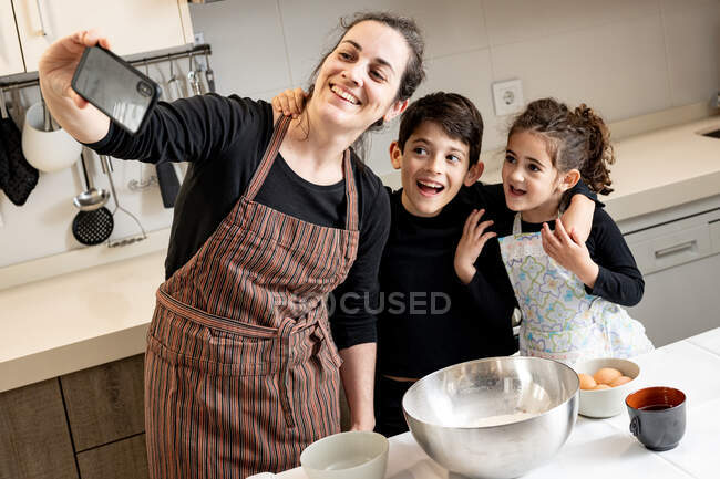 Happy woman in apron smiling and taking selfie with mobile phone with happy children while cooking pastry together in cozy kitchen at home — Stock Photo