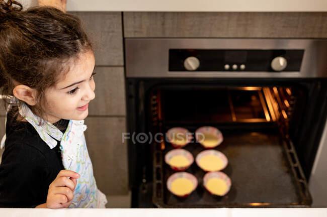 D'en haut adorable fille ethnique dans tablier debout près du four ouvert avec des cupcakes crus et regardant loin tout en cuisinant la pâtisserie dans la cuisine moderne à la maison — Photo de stock