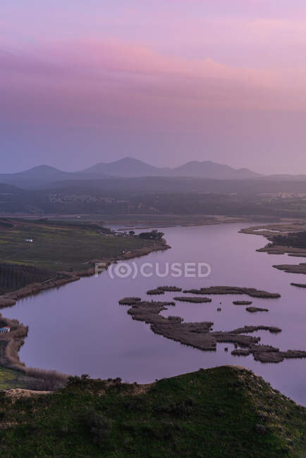 Majestic view of grassy mountain and calm lake located against morning sky in countryside — Stock Photo