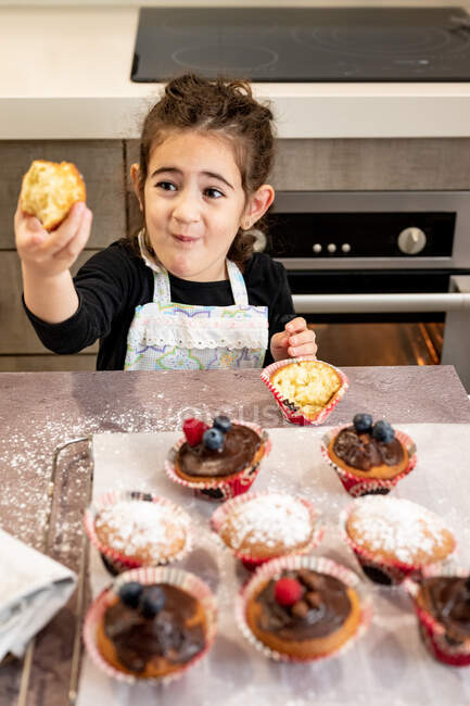 High angle of cute ethnic girl in apron trying freshly baked cupcake while standing near table in cozy kitchen at home — Stock Photo