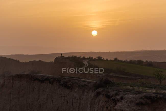 Incredibile paesaggio di montagna con silhouette di persona irriconoscibile contro cielo nuvoloso tramonto — Foto stock