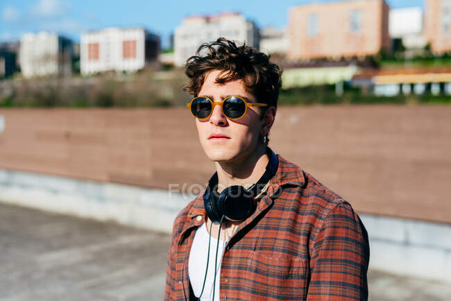 Handsome young man in checkered shirt and sunglasses looking at camera while standing on blurred background of city street — Stock Photo