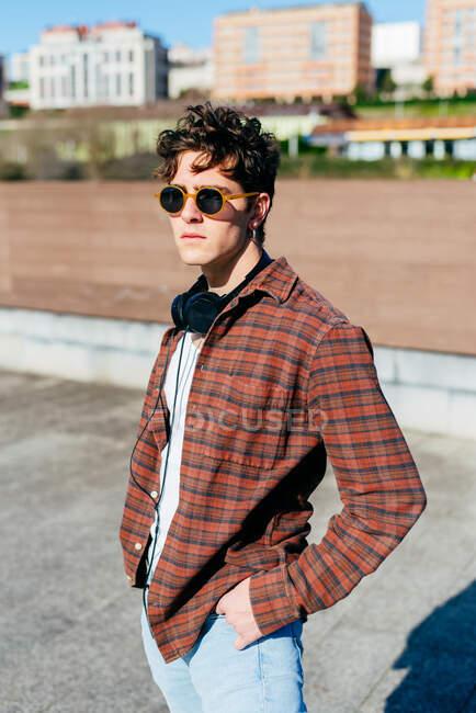 Guapo joven con camisa a cuadros y gafas de sol mirando a la cámara mientras está de pie sobre un fondo borroso de la calle de la ciudad - foto de stock