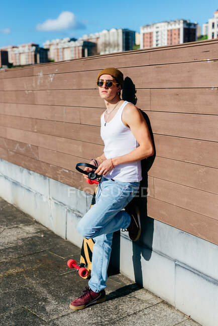 Young handsome male hipster with headphones leaning on wall near skateboard before listening to music on sunny day in city — Stock Photo