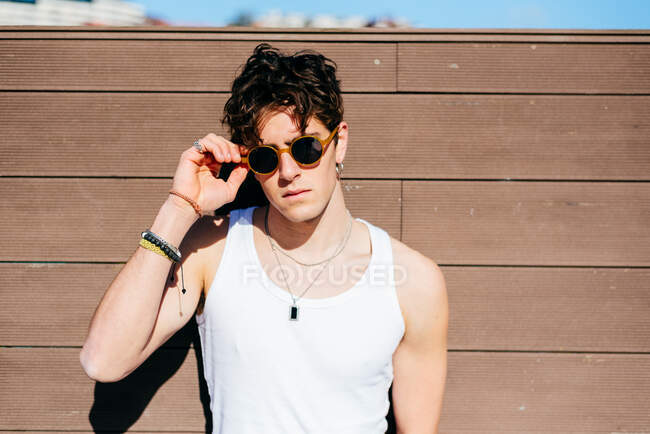 Modern young handsome man in trendy sunglasses and white tank top standing near brown wall on sunny day on city street — Stock Photo