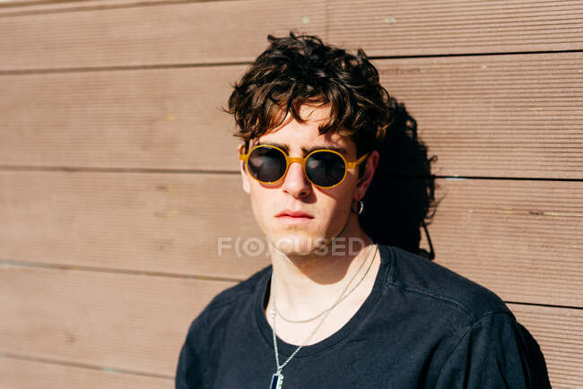 Modern young handsome man in trendy sunglasses and black t-shirt standing near brown wall on sunny day on city street — Stock Photo