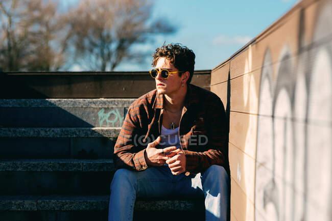 Joven chico guapo en ropa casual mirando hacia otro lado mientras está sentado en las escaleras en el día soleado en la calle de la ciudad - foto de stock