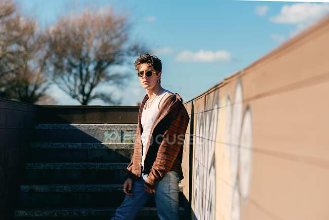 Молодой красивый парень в повседневной одежде смотрит в камеру, стоя на лестнице в солнечный день на городской улице — стоковое фото